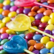 Lollipops lying on colored candies — Stock Photo