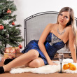 The girl with a glass of champagne and oranges near New Year tree with gift — Stok fotoğraf
