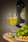 A glass of white wine, green grapes and a bottle of wine on a wooden surfac — Stock Photo
