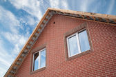 Detail of the facade of a brick house with a roof and windows — Stock Photo