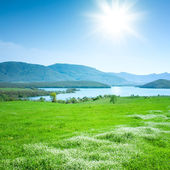 Spring mountain landscape with a lake and meadow — Stock Photo