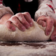 Kneading dough on table — Stock Photo