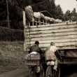 Stock Photo: Men catch ride uphill in Kenya