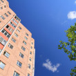 Facade of skyscraper with apartments with blue sky — Stock Photo #8881335