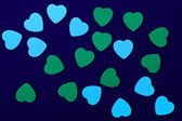 Blue and green hearts on dark blue background — Stock Photo