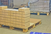 Cardboard boxes on wooden palette — Stock Photo