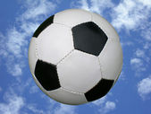 Soccer ball in blue sky — Stock Photo
