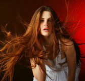 Beautiful woman with long flowing hair on a red background — Stock Photo