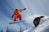 Snowboarder jumping through air with blue sky in background — Stok fotoğraf