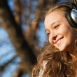 Stock Photo: Beautiful happy girl listening to music