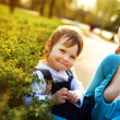 Young mother and looking at daughter outdoors - Stock Photo