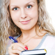 Closeup of a young happy woman writing notes - Stock Photo
