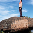 Girl on a rock against the blue sky - Stock Photo
