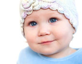 Smiling baby girl showing teeth wearing a hat with flower isolated on white — Stock Photo