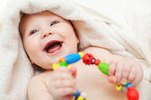 A beautiful smiling baby wrapped in quilt — Stock Photo