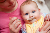 Mother feeding baby food to baby — Stock Photo