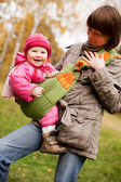 Young mother and looking at daughter outdoors — Stock Photo