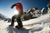 Snowboarder doing a toe side carve with deep blue sky in background — 图库照片