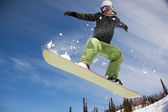Snowboarder jumping through air forest in background — Stock Photo