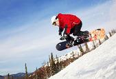 真っ青な空の背景で空気を通って跳躍スノーボーダー — ストック写真