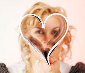 Portrait of cute young woman making heart symbol — Stock Photo