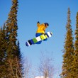 Snowboarder jumping through air with deep blue sky in background — ストック写真