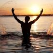 Young man in water. Sunset background - Stock Photo