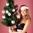 A beautiful young attractive girl in a charming hat of Santa Claus - Stock Photo