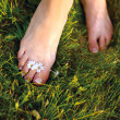 Relaxing woman feet among white flowers — Stock Photo