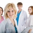 Portrait of doctor with colleagues in the background - Stock Photo