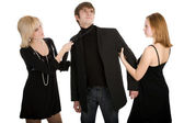 Two women pulling a man in opposite sides — Stock Photo