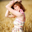 Adorable woman in field with flower - Stock Photo