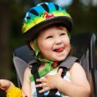 Little girl in the seat bicycle with a helmet on his head — Stock Photo