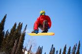 Snowboardista skoky vzduchem s modrou oblohou v pozadí — Stock fotografie