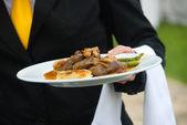Camarero sirviendo comida — Stockfoto