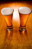 Iki bira bardağı ıslak ahşap zemin üzerinde — Stok fotoğraf