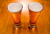 Two beer glasses on wet wooden background — Stock Photo