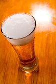 Beer glass over wooden background — Stock Photo