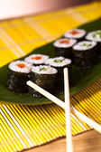 Delicious sushi rolls with chopsticks — Stock Photo