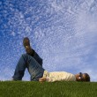Young man lying down on the grass — Stock Photo