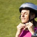 Woman putting a sport helmet — Stock Photo #8357989