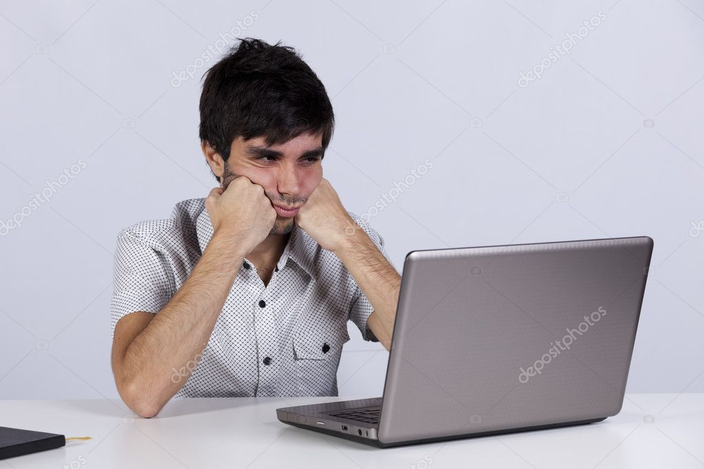 Young men working with his laptop with a bored face — Stock Photo #8356742