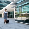 Businesswoman walking with her luggage — Stock Photo