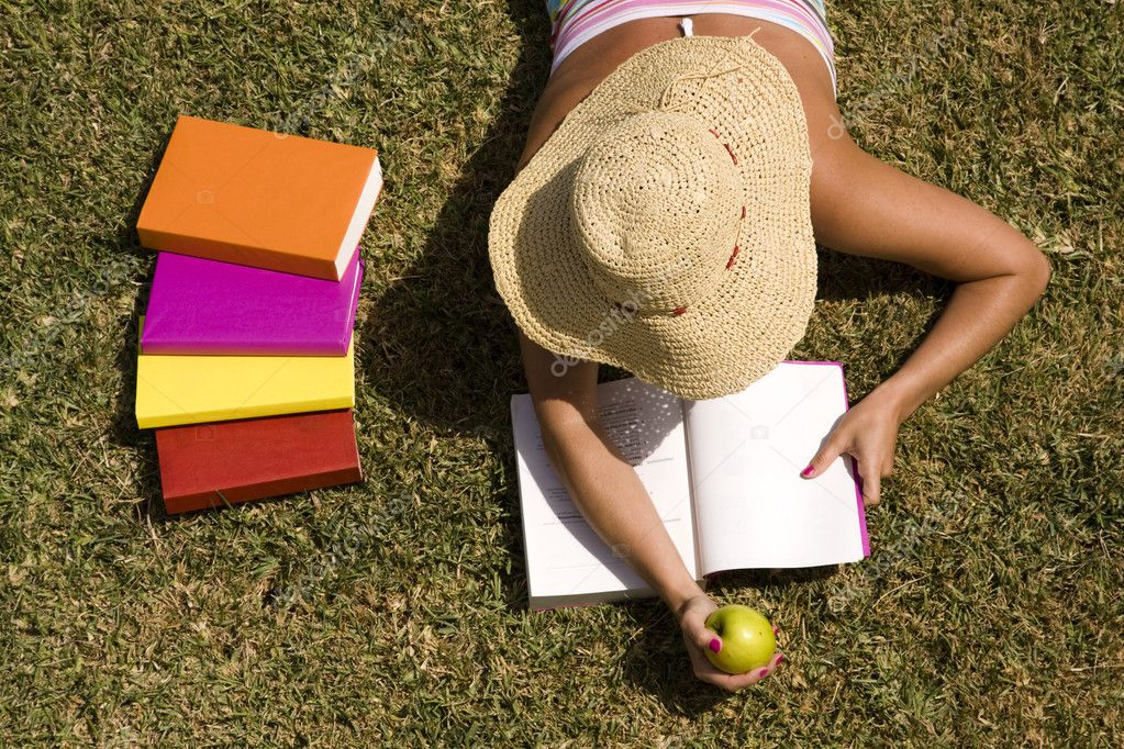 A student relaxing at the grass of the school park (the pages in the book are my self printed) — Stock Photo #8430353