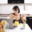 Modern woman reading e-mails at her breakfast — Stock Photo #8444370