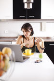 Modern woman reading e-mails at her breakfast — Stok fotoğraf