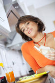 Beautiful woman eating her breakfastl at her kitchen — Stock Photo