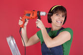 Stressed woman holding a electric drill — Stock Photo