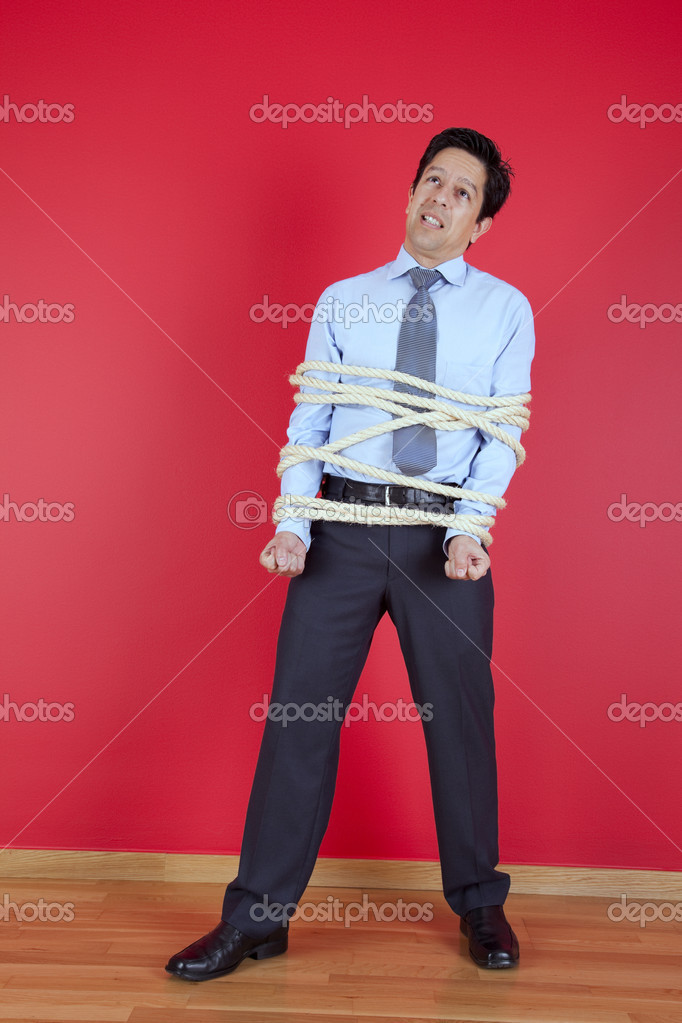 Businessman tied up with a rope struggle to get free — Stock Photo #8573771