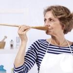 Senior woman tasting food — Stock Photo #8583756